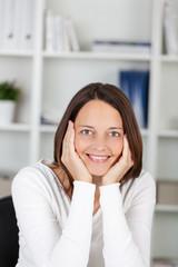 zufriedene frau im büro stützt kopf auf