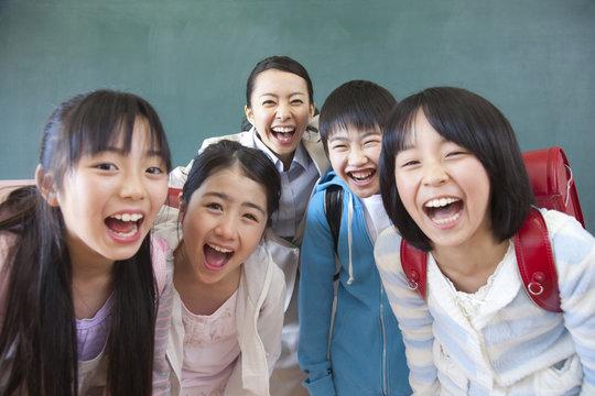 笑顔の小学生男女と女性教師