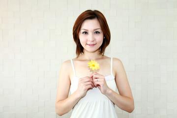 一輪の花を持ち微笑む女性