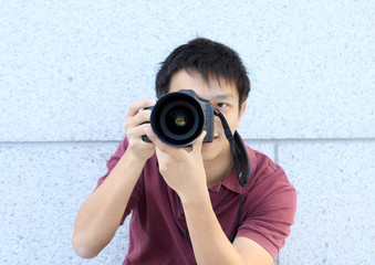 young teenage photographer taking a photo with his DSLR camera.