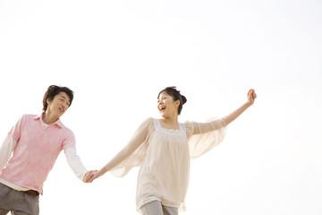 手を繋いで走るカップル