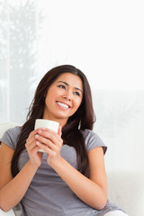 charming woman holding a cup looking at the ceiling