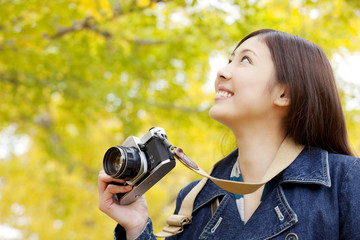 銀杏の下でカメラを持つ女性