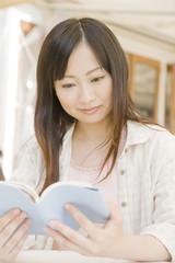 オープンカフェで読書をする女性