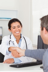 Attractive female doctor shaking a patient's hands