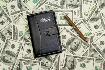 Notepad with money and pen