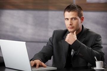 Goodlooking manager sitting at desk in office