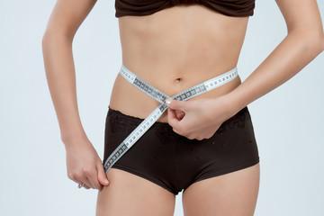 femme mesurant son ventre plat en boxer marron