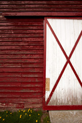 Wall and the door on the old red barn in the countryside.