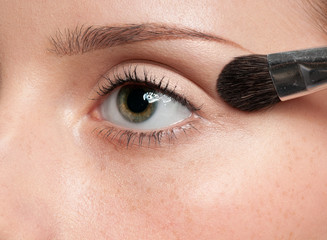 Woman applying cosmetic paint brush on eye zone