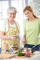 Mother and daughter in kitchen smiling