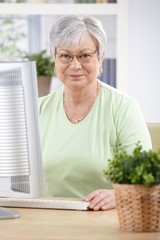 Portrait of elderly woman with computer smiling
