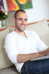 Closeup of handsome man websurfing on laptop computer