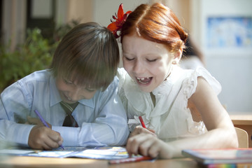 The girl and the boy are drawing