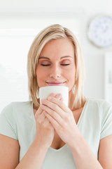 Woman taking in smell of coffee with eyes closed