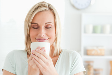Close up of a woman taking in smell of coffee with her eyes clos