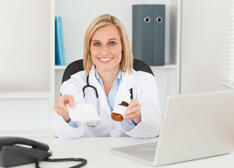 Charming doctor holding prescription and medicine to camera