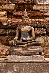 Ruin Buddha statue in front of wall vertical