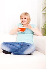 junge Frau mit Müsli zu Hause auf dem Sofa