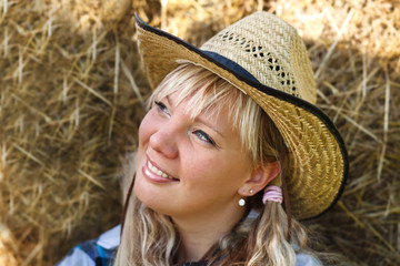 Blonde girl`s portrait in cowboy hat on straw bales background.