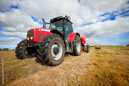 Wall mural tractor collecting haystack in the field