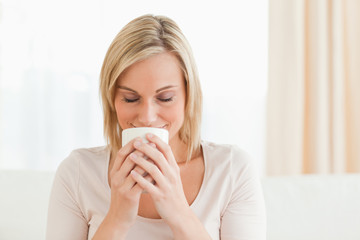 Smiling woman smelling her cup of coffee