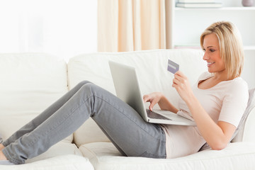 Woman buying online whilie lying on a couch