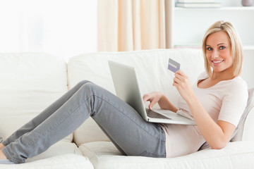 Cute woman buying online whilie lying on a couch