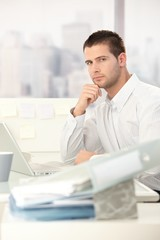 Young casual office worker sitting at desk