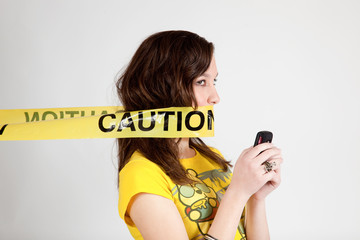 white woman with cell phone and caution tape around mouth