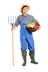 Farmer holding a pitchfork and bucket with vegetables