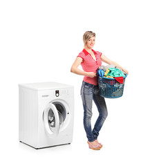 Woman holding a basket and standing next to a washing machine
