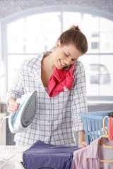 Happy woman talking on phone while ironing
