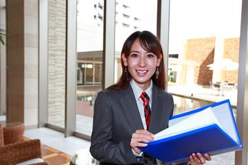 書類を開く笑顔のオフィスレディー
