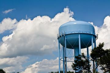 blue water tower under cloudy skies