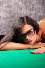 Sensual young lady in sun glasses on a pool table