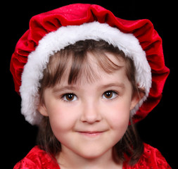 cute little girl in red santa hat and dress smiling close-up. is