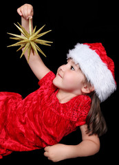 little girl laying on ground holding golden Chritsmas ornament