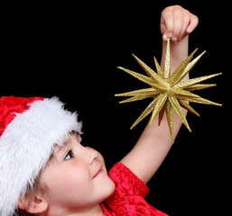 close-up of little girl in santa hat holding up golden christmas
