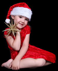 pretty little girl in Santa hat posing with golden star. isolate