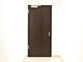 braune Holztür mit Knauf in hellem Flur