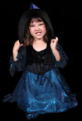 sweet little girl dressed as a witch making a scary face