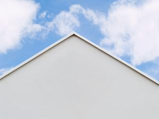 Hausdach, Dachfirst mit blauem Himmel und Wolken