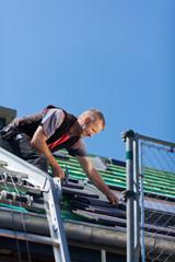 dachdecker legt dachziegel