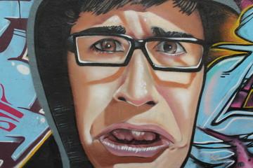 chico indignado con gafas de pasta graffiti