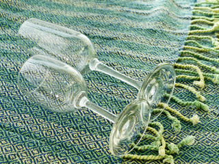 Two empty stemmed glasses on Thai cloth