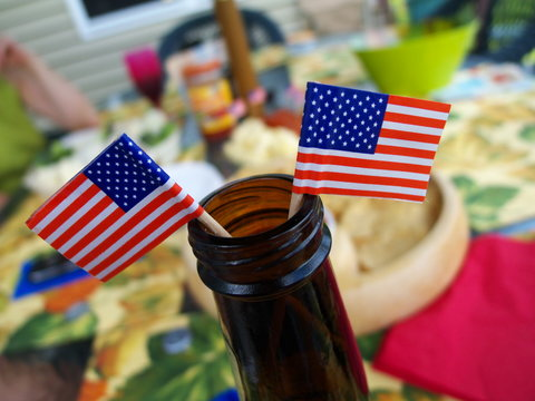 Two American flags planted in the top of a beer bottle at picnic