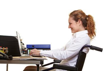 Rollstuhlfahrerin arbeitet an Schreibtisch