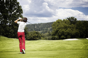 Woman teeing-off golf ball.