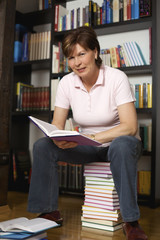 Smiling senior woman sitting on book stack
